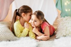 Happy girls lying in kids tent and talking at home. Childhood, hygge and friendship concept - happy girls lying in kids tent and gossiping at home stock photography