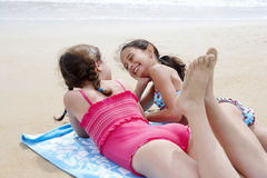 Happy Girls Lying On Towel At Beach Stock Images