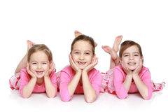 Happy girls lying on a white background Stock Images