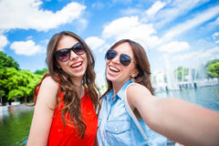Happy girls making selfie background big fountain. Young tourist friends traveling on holidays outdoors smiling happy. Royalty Free Stock Photo