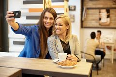 Happy girls making selfie. Happy attractive girls making self portrait by mobilephone in cafeteria Stock Photography