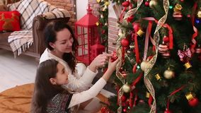Happy girls, mother and daughter decorating Christmas tree at home. Happy girls, mother and daughter decorating a Christmas tree at home stock footage