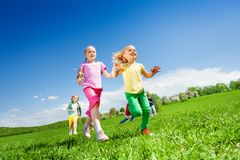 Happy girls and other kids running in green field. Happy girls and other kids running in the green field during daytime and sunny beautiful weather Royalty Free Stock Image