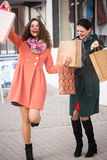 Happy girls with packages during shopping. Beautiful happy girls with packages during shopping Stock Photos