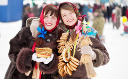 Happy girls with pancake during Shrovetide. Happy girls in russian traditional clothes with pancake and round cracknel during Shrovetide royalty free stock photography