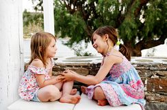 Happy girls playing. Two happy young girls playing outdoors with sea or lake and leafy green tree in background Royalty Free Stock Image