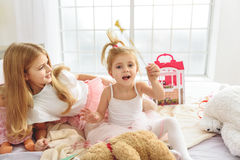 Happy girls playing in bedroom. Little fairy is waving her magic wand mysteriously. Her elder sister is looking at her with interest. Children are sitting on bed Stock Photography