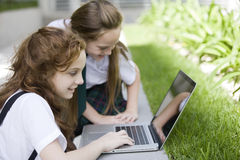 Happy girls playing with computer Stock Images