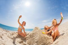 Happy girls playing sand games at tropical beach. Portrait of three happy girls in swimwear playing sand games at tropical beach at sunny day Stock Photos
