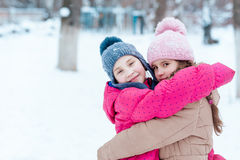 Happy girls playing on snow in winter Royalty Free Stock Images