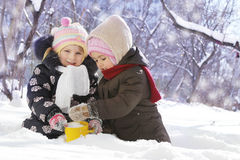 Happy girls playing in snowy park Stock Photography