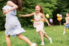 Happy girls playing tag game at birthday party Stock Photos