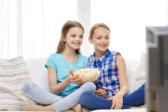 Happy girls with popcorn watching tv at home. People, children, television, friends and friendship concept - two happy little girls with popcorn watching tv at Stock Photo