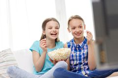 Happy girls with popcorn watching tv at home. People, children, television, friends and friendship concept - two happy little girls watching comedy movie on tv Stock Photo