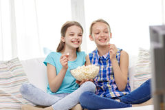 Happy girls with popcorn watching tv at home. People, children, television, friends and friendship concept - two happy little girls watching comedy movie on tv Royalty Free Stock Image