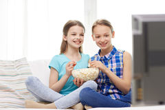 Happy girls with popcorn watching tv at home Royalty Free Stock Images