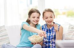 Happy girls with popcorn watching tv at home. People, children, television, friends and friendship concept - two happy little girls watching tv and eating Stock Image