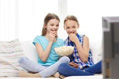 Happy girls with popcorn watching tv at home. People, children, television, friends and friendship concept - two happy little girls watching tv and eating Stock Photo