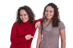 Happy girls: Portrait of real female twins wearing winter pullover. Happy girls: Portrait of real female twin women wearing wool winter pullover royalty free stock photography