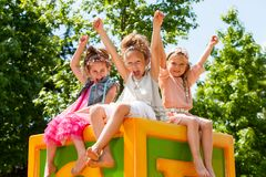 Happy girls raising arms together in park. Stock Image