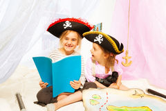 Happy girls reading book about pirate's treasures. Two happy girls in pirate's costumes, reading blanked book about pirate's treasures Royalty Free Stock Images