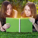 Happy girls reading a book. Two young happy smiling girls reading a book in a summer green park. Education concept Royalty Free Stock Images