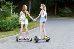 Two pretty happy girls riding on hover board or gyroscooter outdoors at sunset in summer. Active life concept. Happy girls riding on hover board or gyroscooter Stock Photo