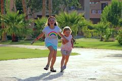 Happy girls run on footpath in tropical resort stock photos