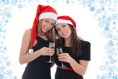 Happy girls in santa hats with champagne Stock Photography