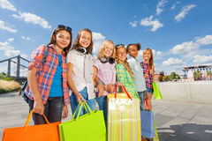Happy girls with shopping bags stand together Stock Photo