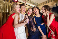 Happy girls singing into a microphone Royalty Free Stock Photography