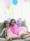 Happy Girls Sitting On Sofa In Party Costumes. Portrait of two happy young girls sitting on sofa in party costumes Stock Photography