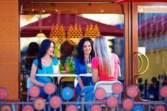 Happy girls sitting on summer cafe terrace Royalty Free Stock Image