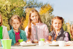 Happy girls sitting at table outside with cups Stock Photo