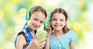 Happy girls with smartphone and headphones Stock Photo