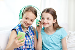 Happy girls with smartphone and headphones Royalty Free Stock Photo