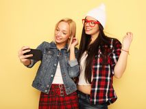 Happy girls  with smartphone  over yellow background. Happy self Stock Images