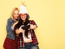 Happy girls  with smartphone  over yellow background. Happy self Stock Photo