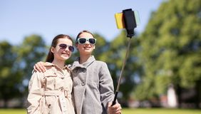 Happy girls with smartphone selfie stick in park Stock Photography