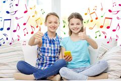 Happy girls with smartphone sitting on sofa Stock Photography