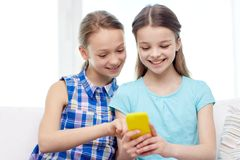 Happy girls with smartphone sitting on sofa Royalty Free Stock Photos