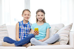 Happy girls with smartphone sitting on sofa Royalty Free Stock Photo