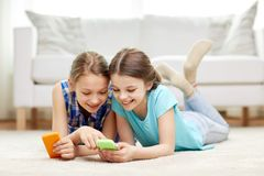 Happy girls with smartphones lying on floor. People, children, technology, friends and friendship concept - happy little girls with smartphones lying on floor at Stock Photography