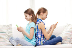 Happy girls with smartphones sitting on sofa Royalty Free Stock Image