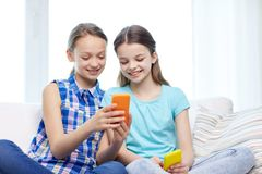 Happy girls with smartphones sitting on sofa Royalty Free Stock Images