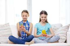 Happy girls with smartphones sitting on sofa Stock Photos