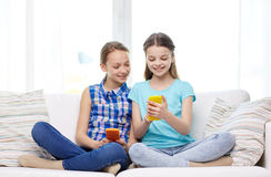 Happy girls with smartphones sitting on sofa Royalty Free Stock Photography