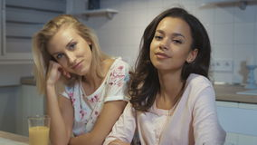 Happy girls smiling at camera while sitting in the kitchen. Portrait of two multi-ethnic girls wearing pajamas at home stock footage