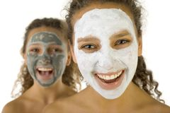 Happy girls with spa mask. Happy young women with masks anti-aging. Focus on first person. They're on white background Stock Photo