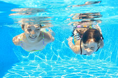 Happy girls swim underwater in pool Stock Photos